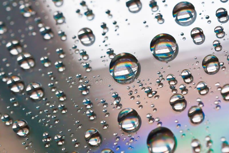 Gotitas de agua en la superficie de un disco compacto. imagen de archivo