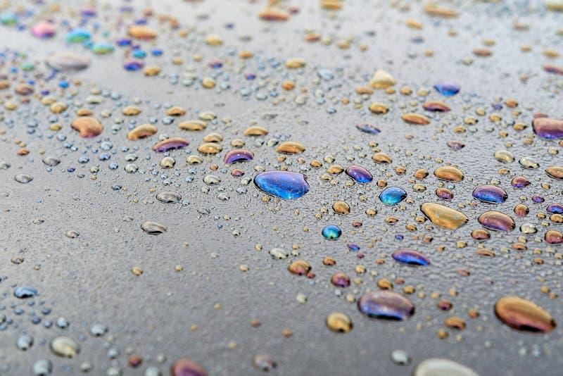 Gotitas de agua y productos derivados del petróleo en la superficie oscura, puntos coloreados en la superficie imagenes de archivo