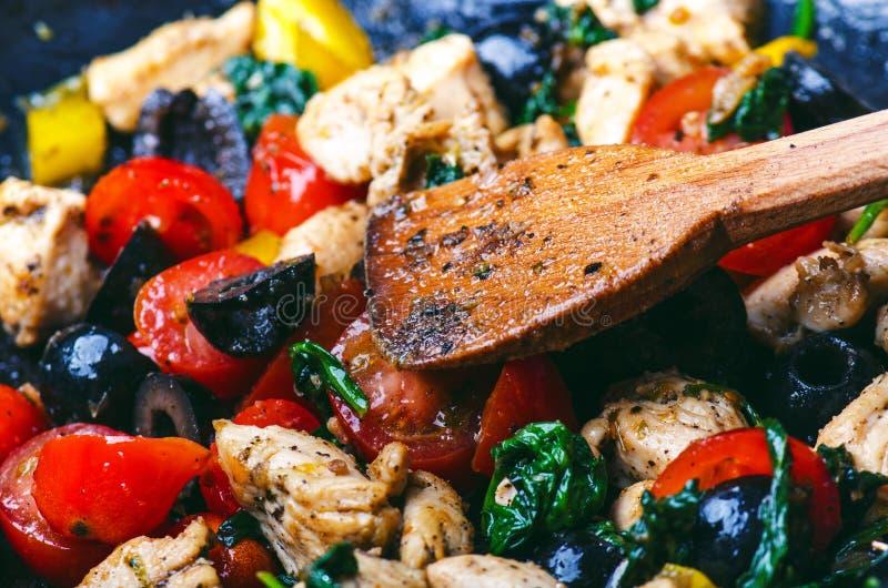 Gotować jedzenie na niecce Oliwka, rżnięta kurczak pierś, pomidory, chłodny, pieprzowy, spinacy i ziele zdjęcia stock
