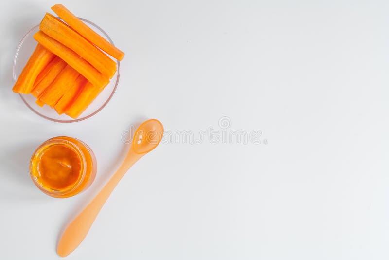 Gotować mashed marchewki dla dziecka na białego tła odgórnym widoku fotografia stock