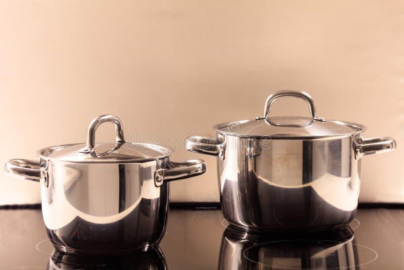 Gotować puszkuje nierdzewnego umieszczającego na nowożytnej ceramicznej kuchence Odbicia, zakończenie up, szczegóły obrazy royalty free