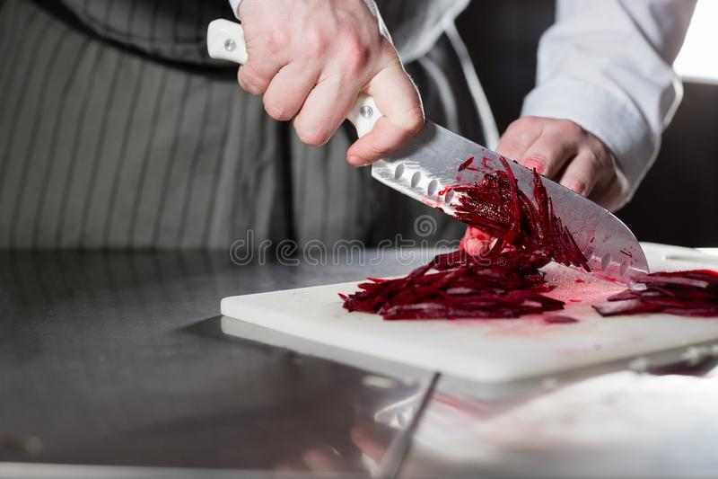 Gotować w restauracyjnej kuchni Zbliżenie ręka z nożowym tnącym świeżym warzywem Młodego szefa kuchni tnący burak na bielu zdjęcia royalty free