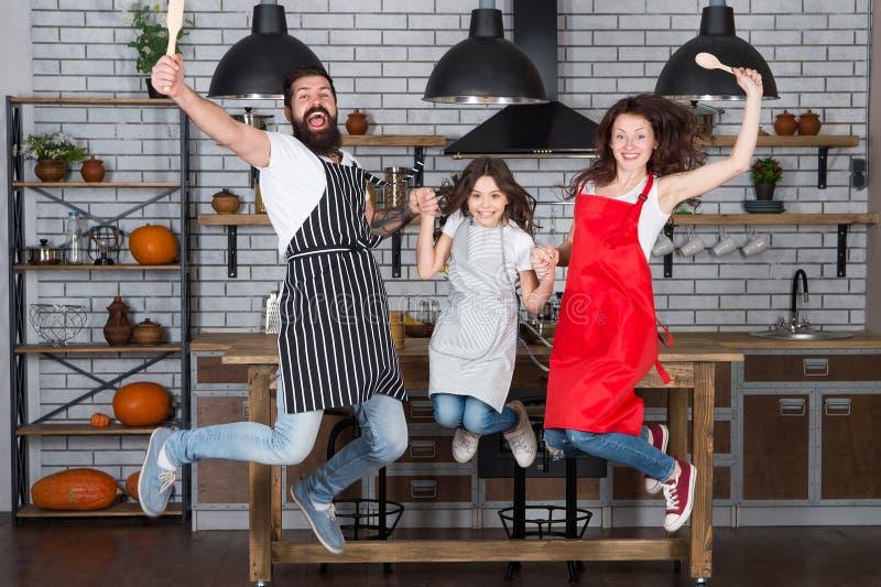 Gotować z dzieckiem można być zabawą Mie? zabaw? w kuchni Rodzinny mama tata i mali c?rki odzie?y fartuchy skaczemy w kuchni obrazy stock