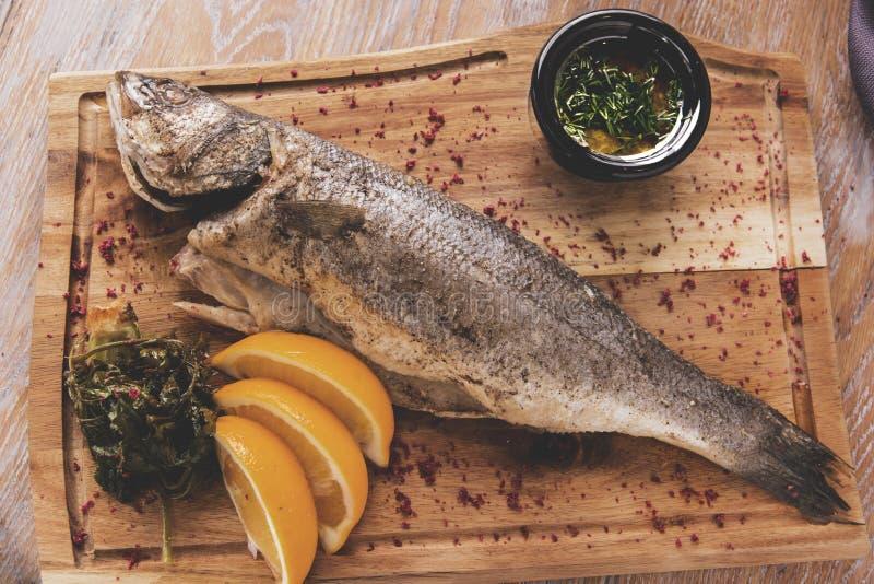 Gotowana dennego basu ryba na desce z kumberlandami fotografia stock