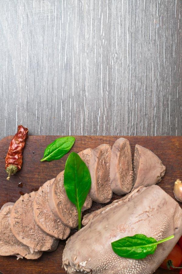 Gotowana wołowina, wieprzowina jęzor z pomidorami, basilu liść, studio strzał, odizolowywający na drewnianym tle zdjęcie royalty free