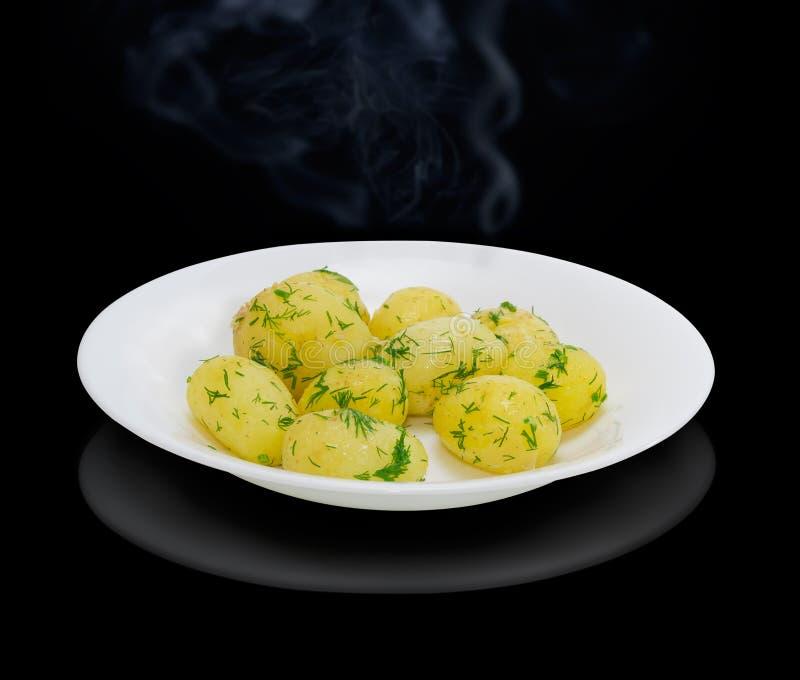 Gotowane młode grule z masłem i koperem na ciemnym tle fotografia stock