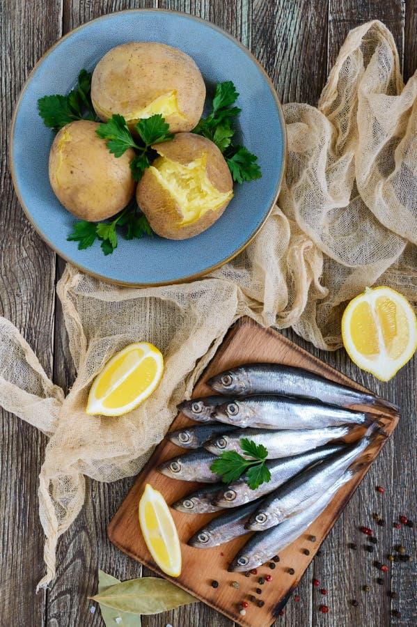 Gotowane unpeeled grule w skórach, mała solona ryba Bałtycki śledź, brzdąc na drewnianym stole zdjęcie royalty free