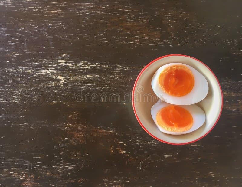 Gotowani jajka dzielą w dwa kawałka w filiżance na drewnianym stole fotografia royalty free