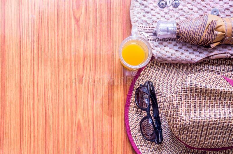 gotowy do Odgórnego widoku plaży tło istotni nowożytni lato kobiet akcesoria w drewnianym stole Okulary przeciwsłoneczni, parasol zdjęcie royalty free