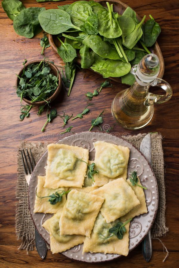 Gotowy pierożek w talerzu, szpinak, oliwa z oliwek w słoju obraz stock