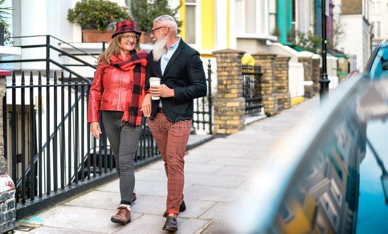Gott överordnat par som går hand i hand i Notting Hill i London City - Aktiv äldre och konceptet för reselivsstil royaltyfri foto