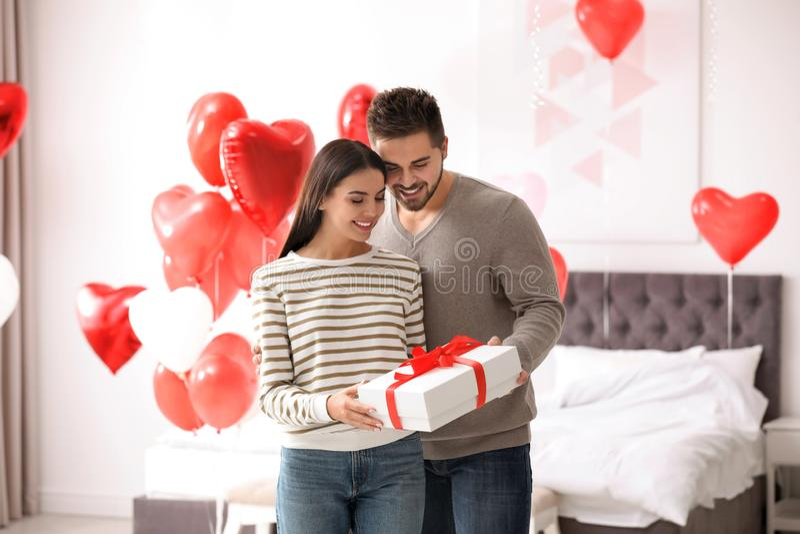 Gott ungt par i sovrummet som dekorerats med hjärtballonger Alla hjärtans dag royaltyfri foto