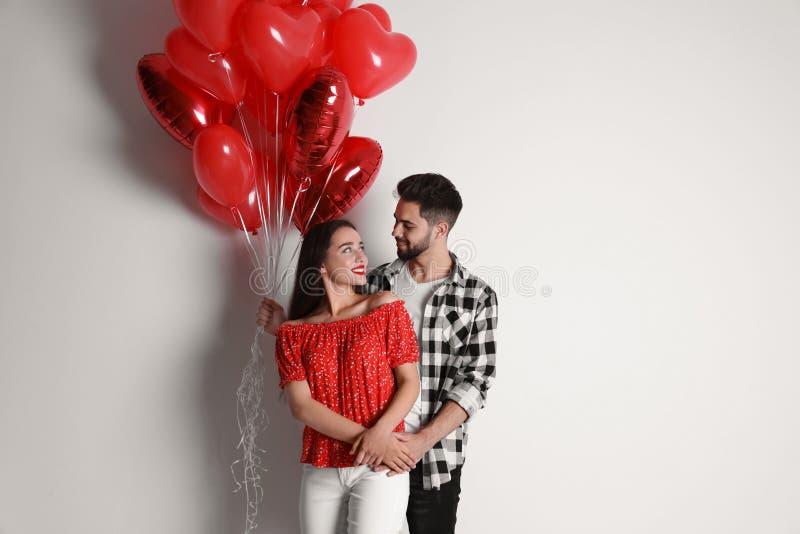Gott ungt par med hjärtformade ballonger i bakgrunden Alla hjärtans dag royaltyfria foton