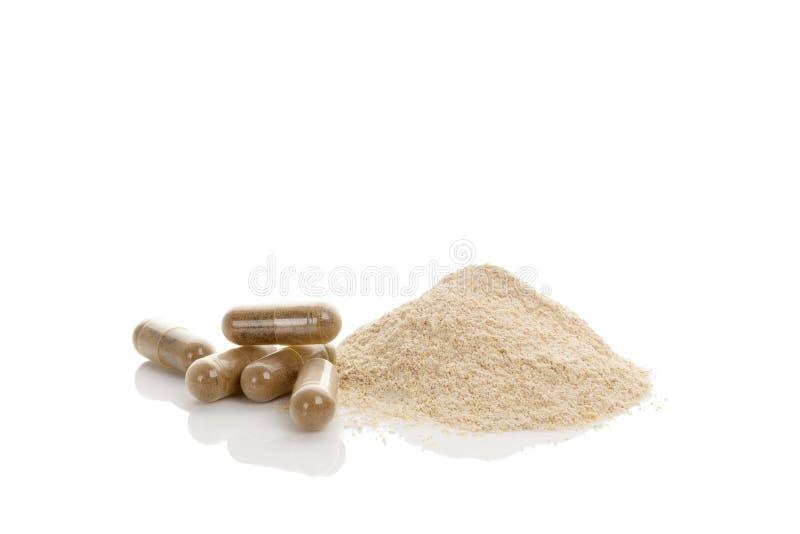 Gotu kola gel capsules and heap of powder. Herbal remedy on white background royalty free stock photos