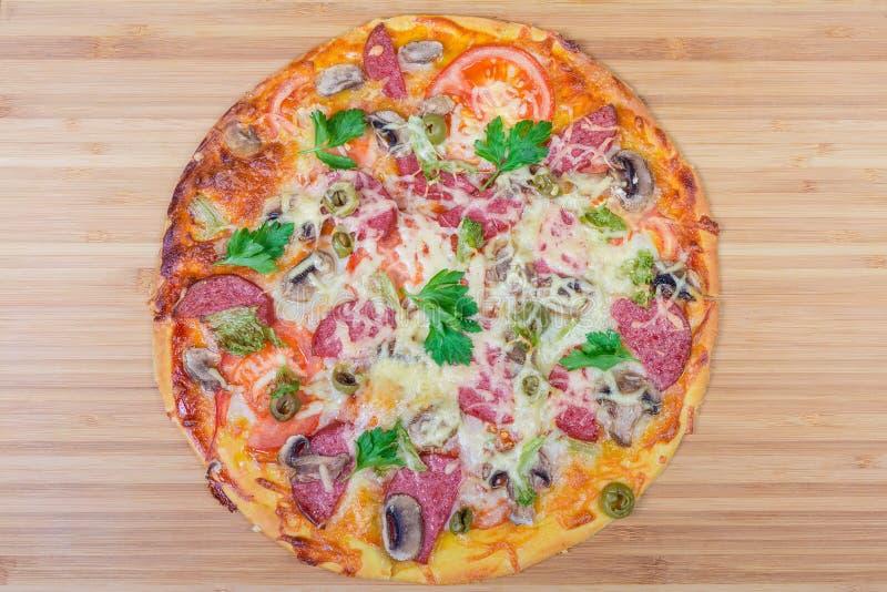 Gotująca pizza z salami na w górę drewnianej tnącej deski zdjęcie stock