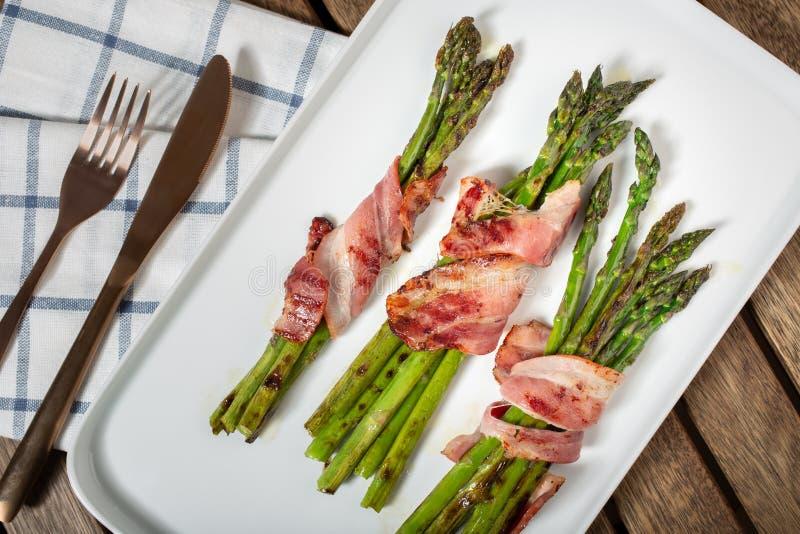 Gotuj?cy asparagus z zawijaj?cym bekonem na talerzu zdjęcia royalty free