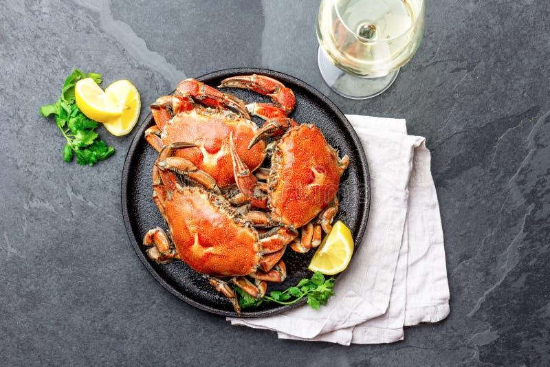 Gotujący cali kraby na czarnym talerzu słuzyć z białym winem, czerni łupkowy tło, odgórny widok fotografia royalty free