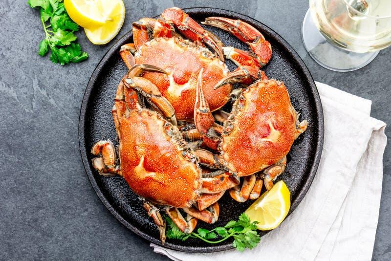 Gotujący cali kraby na czarnym talerzu słuzyć z białym winem, czerni łupkowy tło, odgórny widok zdjęcia royalty free