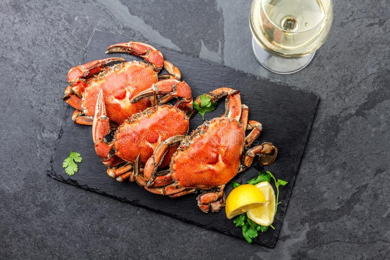 Gotujący cali kraby na czarnym talerzu słuzyć z białym winem, czerni łupkowy tło, odgórny widok fotografia stock