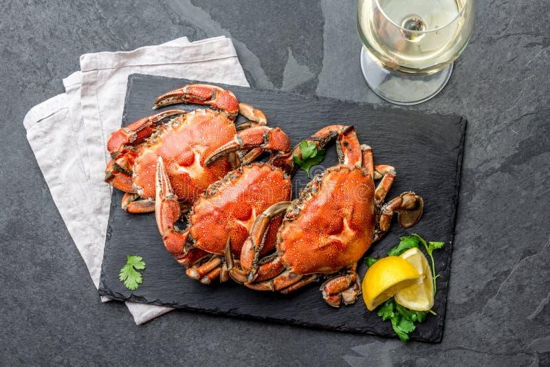 Gotujący cali kraby na czarnym talerzu słuzyć z białym winem, czerni łupkowy tło, odgórny widok zdjęcia stock
