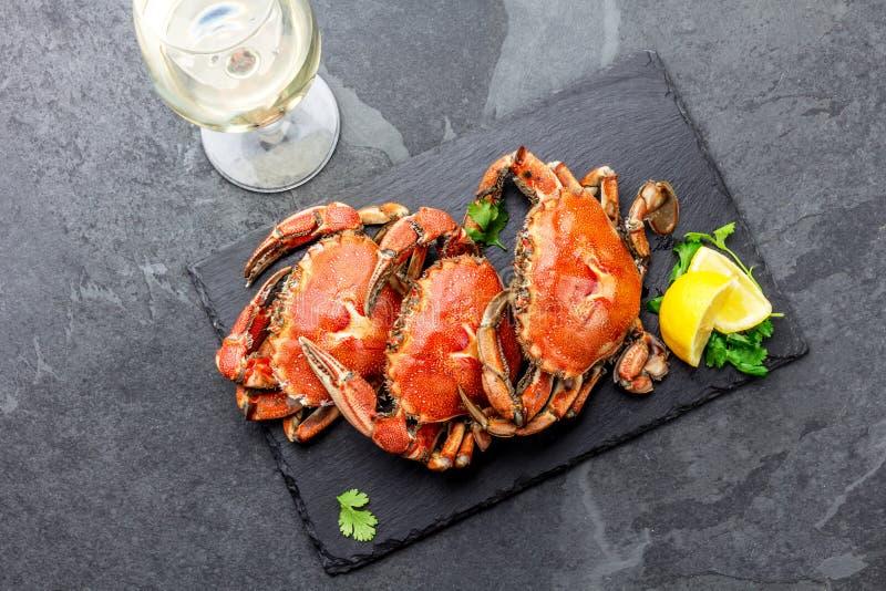 Gotujący cali kraby na czarnym talerzu słuzyć z białym winem, czerni łupkowy tło, odgórny widok obraz royalty free