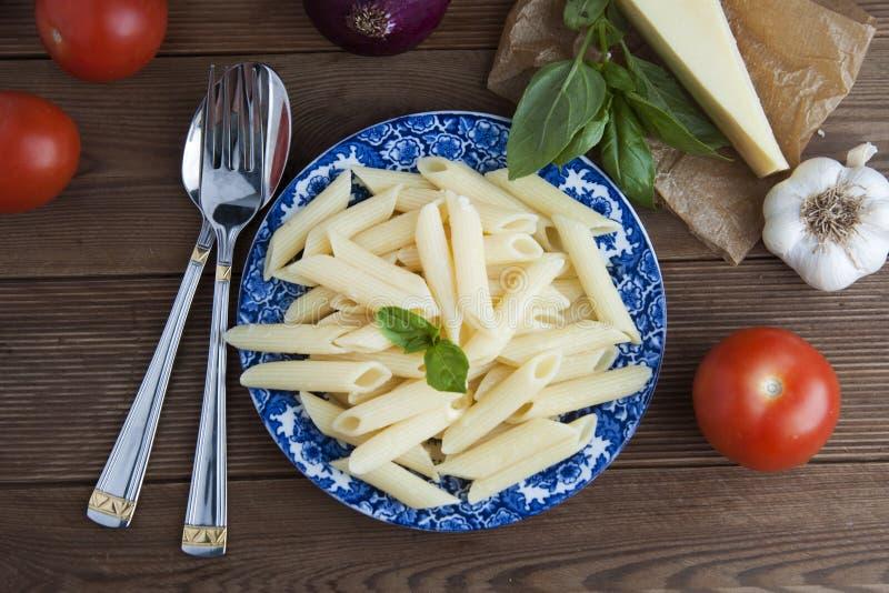 Gotujący penne makaron z masła, serowego i świeżego warzywa składnikami na tle: pomidor, czosnek, cebula, rozwidlenie i łyżka, ba obraz stock