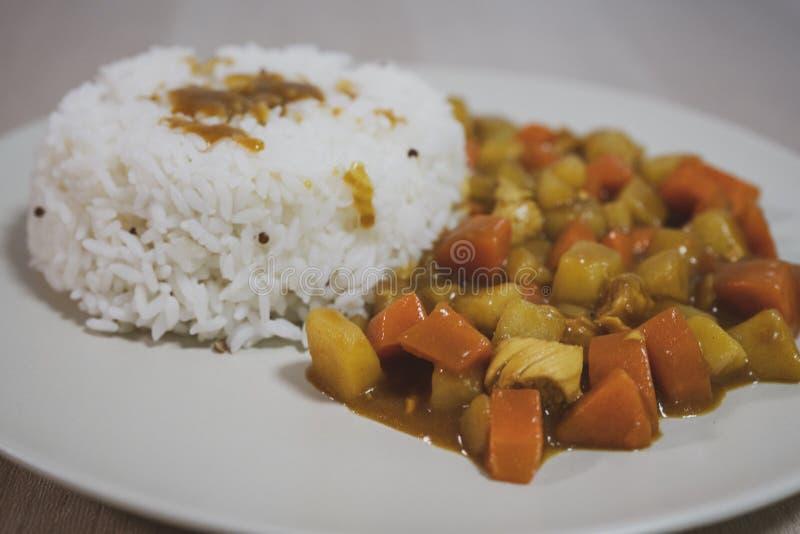 Gotujący ryż, curry z kurczakiem, marchewka i grula w górę talerza na stole, dalej fotografia royalty free