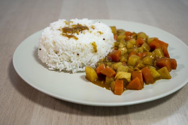 Gotujący ryż, curry z kurczakiem, marchewka i grula w górę talerza na stole, dalej obraz royalty free