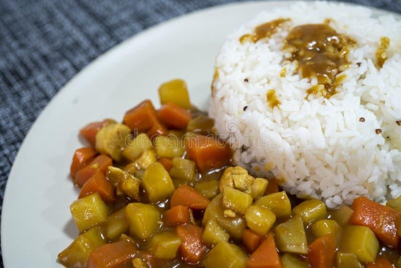 Gotujący ryż, curry z kurczakiem, marchewka i grula w górę talerza na stole, dalej obrazy royalty free