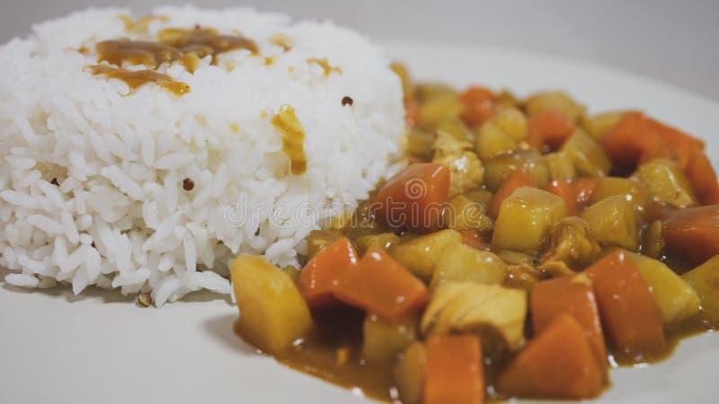 Gotujący ryż, curry z kurczakiem, marchewka i grula w górę talerza na stole, dalej obraz stock