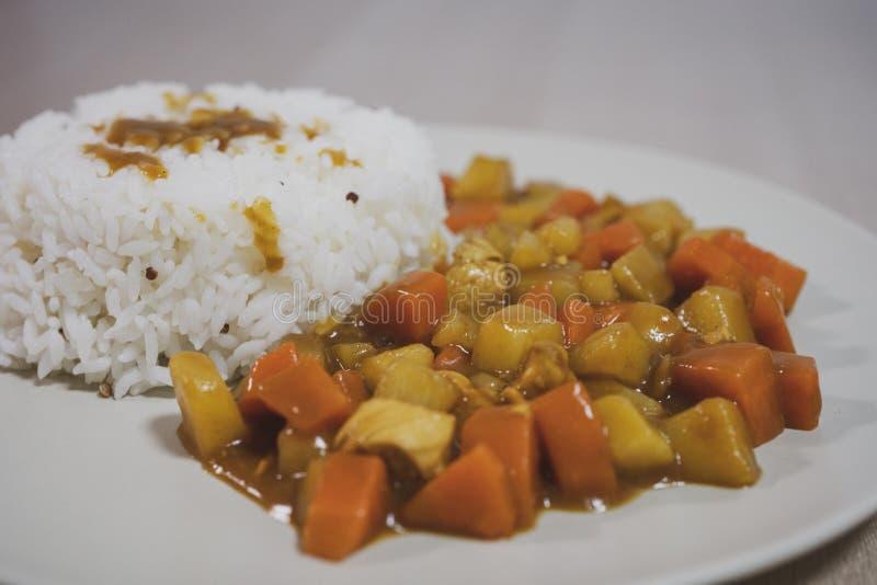 Gotujący ryż, curry z kurczakiem, marchewka i grula w górę talerza na stole, dalej zdjęcie stock