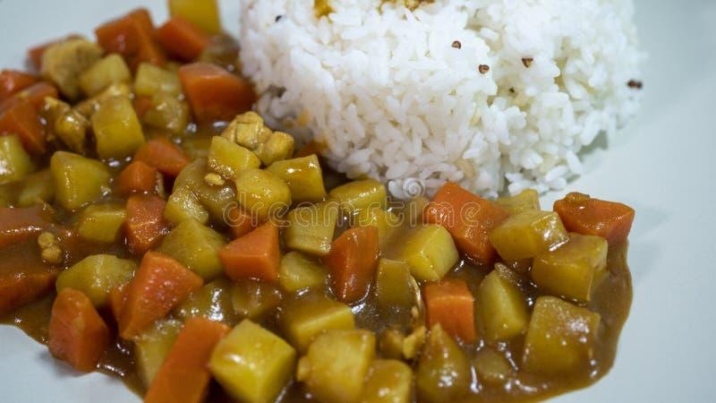 Gotujący ryż, curry z kurczakiem, marchewka i grula w górę talerza na stole, dalej zdjęcie royalty free