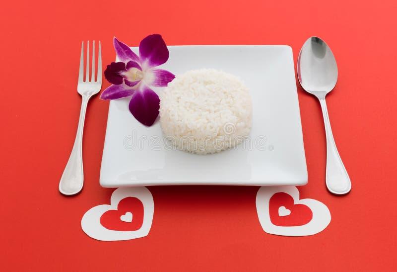 Gotujący ryż z łyżką i rozwidlenie na białej orchidei i naczyniu obrazy stock