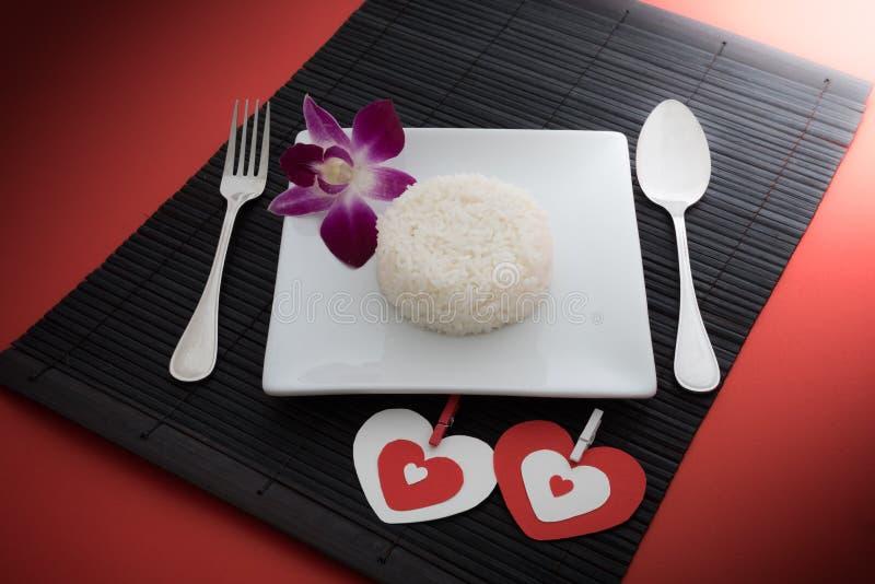 Gotujący ryż z łyżką i rozwidlenie na białej orchidei i naczyniu zdjęcia stock
