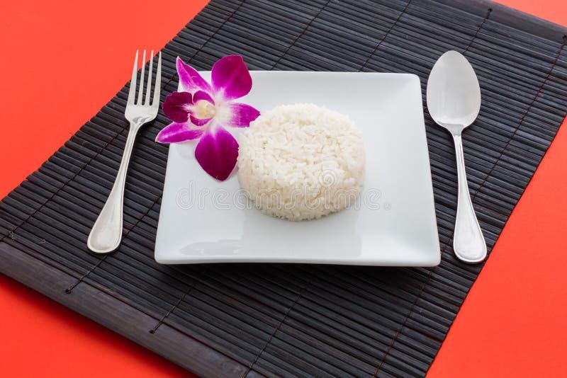 Gotujący ryż z łyżką i rozwidlenie na białej orchidei i naczyniu zdjęcie stock