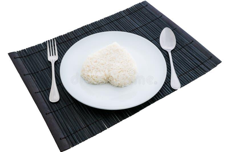 Gotujący ryżowy serce kształtuje z rozwidleniem na białym naczyniu i łyżką fotografia stock
