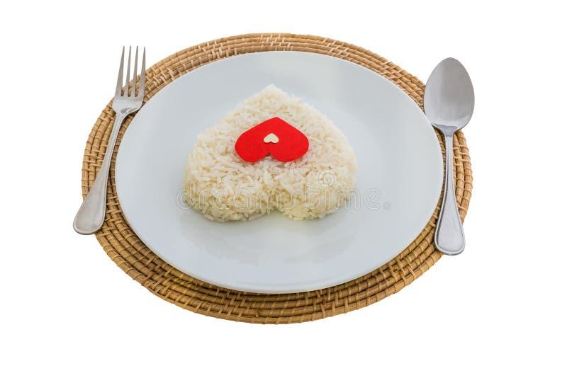 Gotujący ryżowy serce kształtuje z rozwidleniem na białym naczyniu i łyżką fotografia royalty free