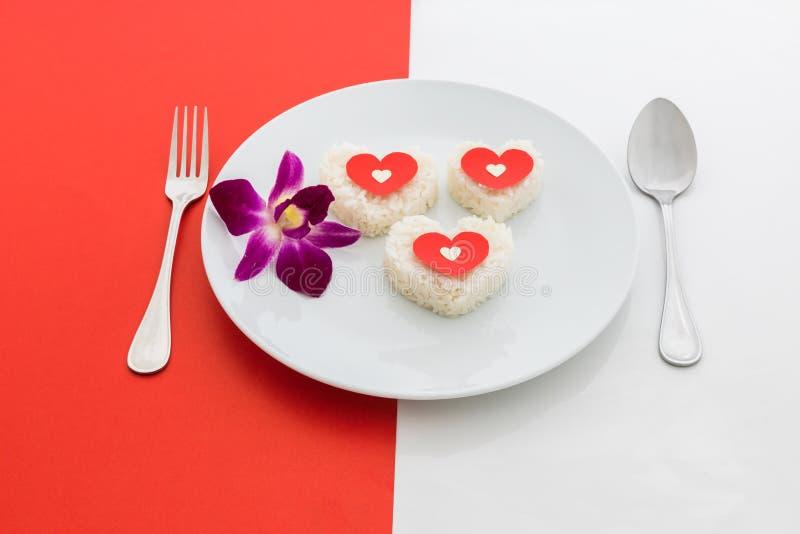 Gotujący ryżowy serce kształtuje z rozwidleniem na białym naczyniu i łyżką i obrazy stock