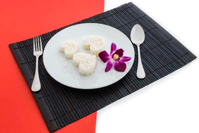 Gotujący ryżowy serce kształtuje z rozwidleniem na białym naczyniu i łyżką i obraz royalty free