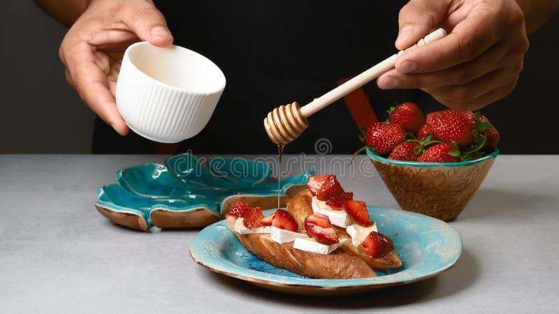 Gotujący szef kuchni rękami - bruschetta kanapki z truskawką, serem i miodem na całości adry, piec chleb fotografia stock