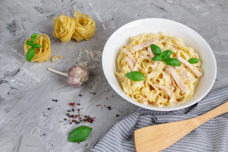 Gotujący tagliatelle makaron na talerzu z Carbonara kumberlandem, bekonem, basilem i Parmezańskim serem, Włochy jedzenie fotografia royalty free