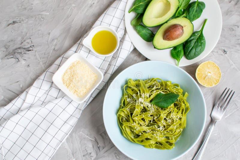 Gotujący zielony szpinaka tagliatelle makaron na talerzu z Parmezańskiego sera i avocado kumberlandem, Włochy jedzenie fotografia royalty free