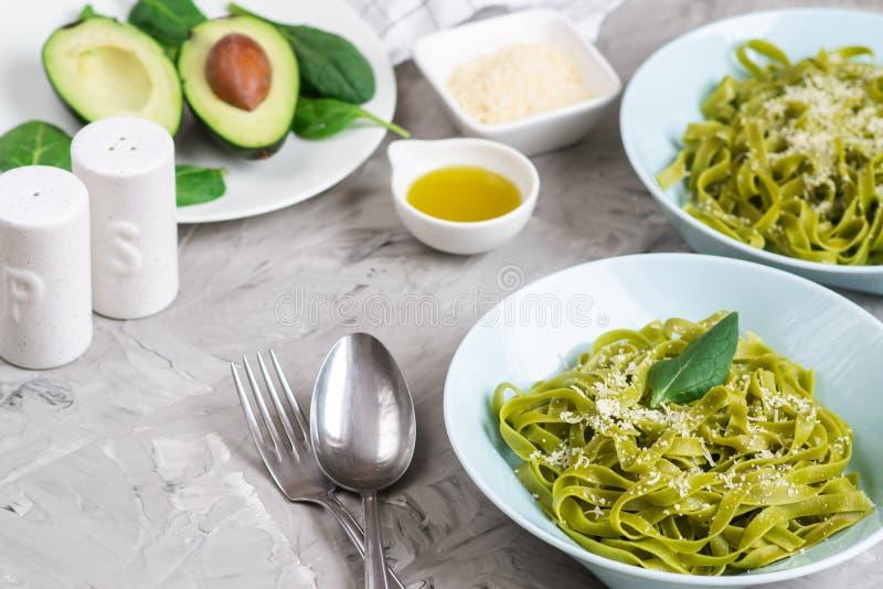 Gotujący zielony szpinaka tagliatelle makaron na talerzu z Parmezańskiego sera i avocado kumberlandem, Włochy jedzenie zdjęcie stock
