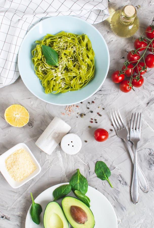 Gotujący zielony szpinaka tagliatelle makaron na talerzu z Parmezańskiego sera i avocado kumberlandem, Włochy jedzenie obrazy stock