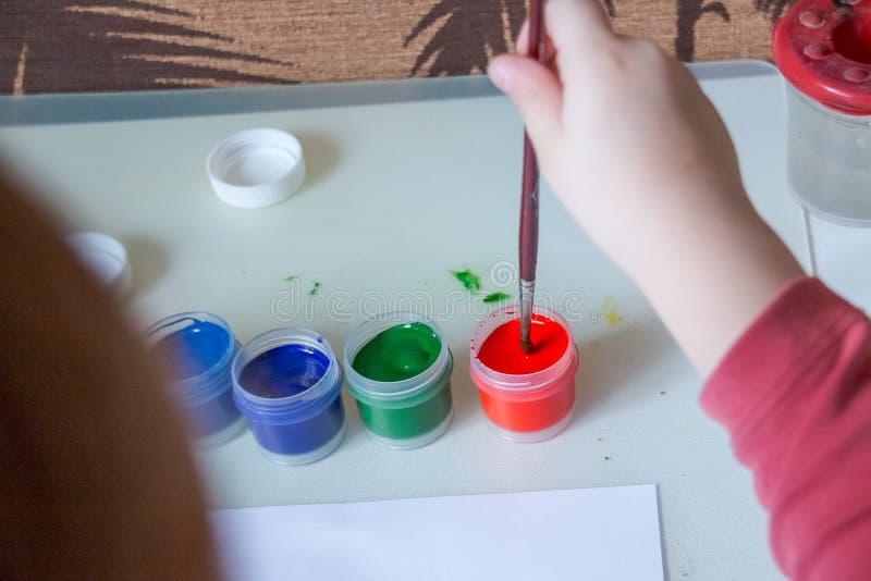 Gouache och vatten för att måla och ungeteckning på vitbok barn som gör konstverk barnet doppade hans borste i arkivfoton