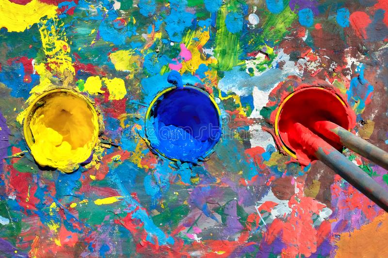 Gouache paint table with paint smears and cups with yellow, blue royalty free stock images
