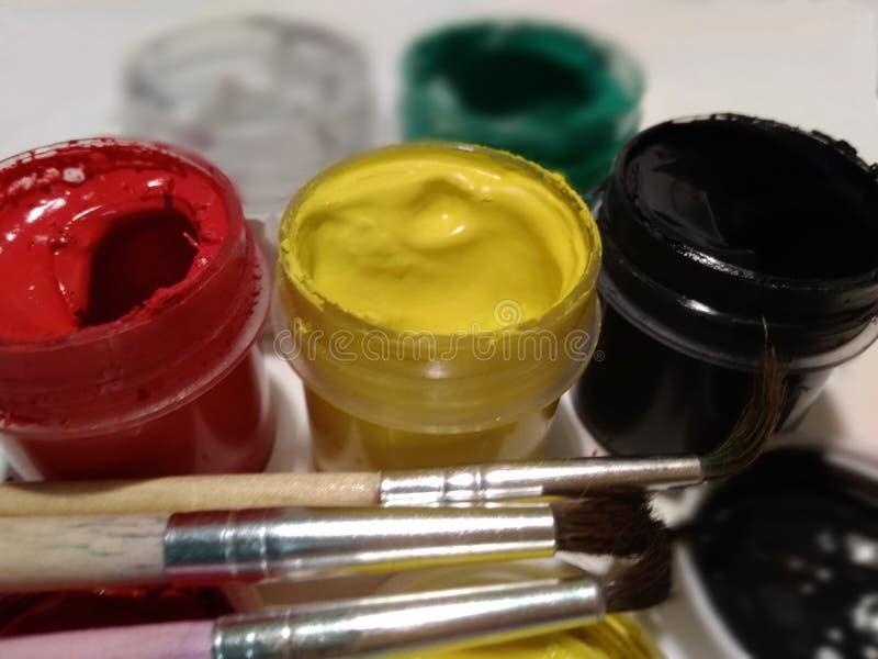 Gouachemålarfärger och målarfärgborstar royaltyfri foto
