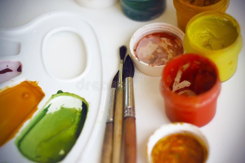 Gouacheverven, borstels en een palet voor het mengen van kleuren stock afbeelding