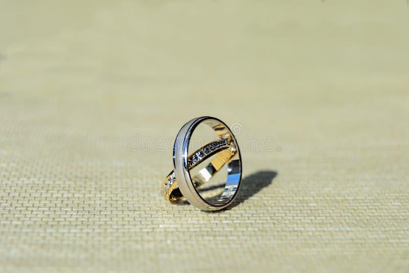 Goud en zilveren bruiloftringen over duidelijke en ruwe oppervlakte Licht achtergrond en zonlicht Duidelijke schaduwen 01 royalty-vrije stock foto