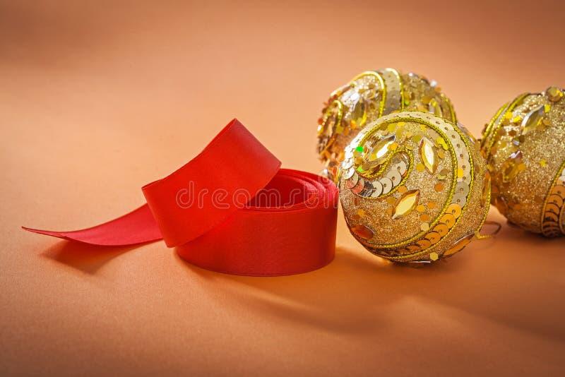 Goud gekleurde Kerstmissnuisterijen en rood lint op lichtbruine bac royalty-vrije stock afbeelding